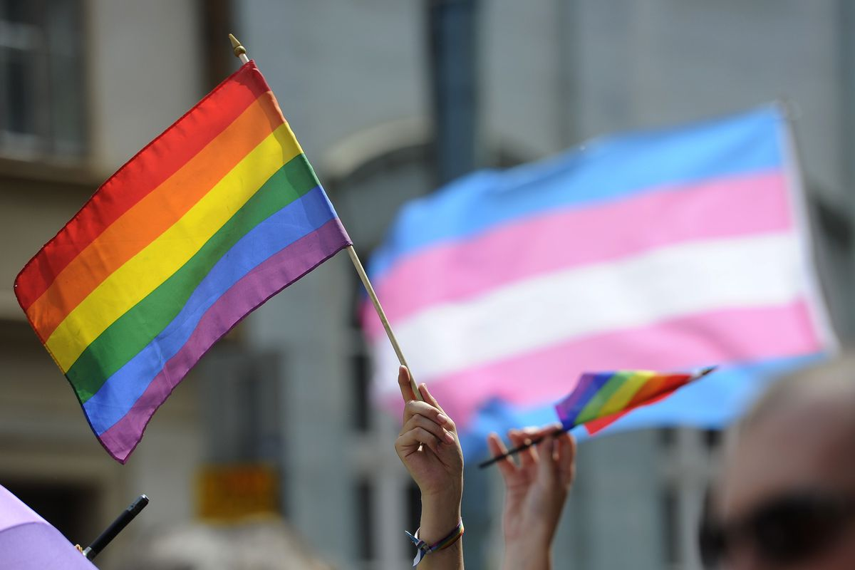 The LGBTQ flag, with the transgender flag in the background.