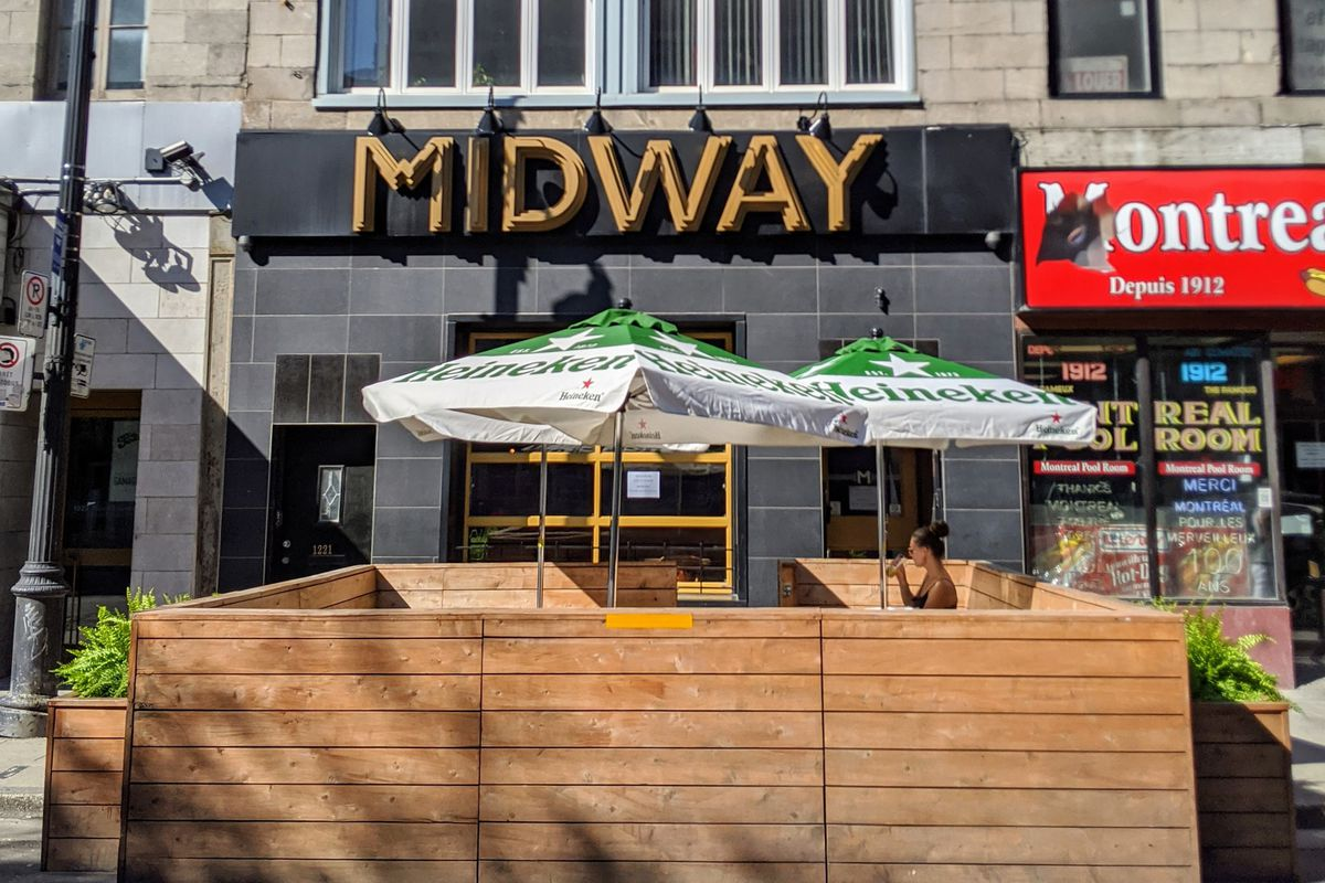 """person sitting at wooden patio under """"Midway"""" sign"""