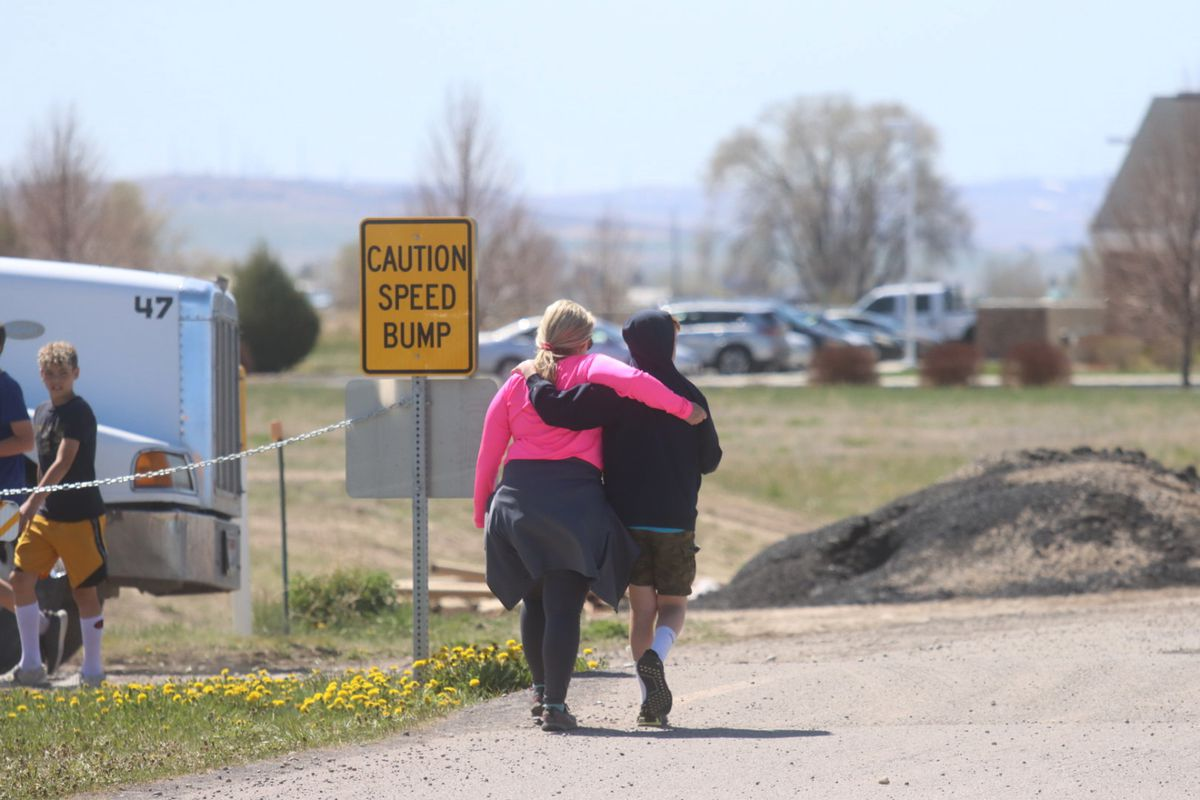Two people walk together near the scene of a shooting at an eastern Idaho middle school in Rigby, Idaho.