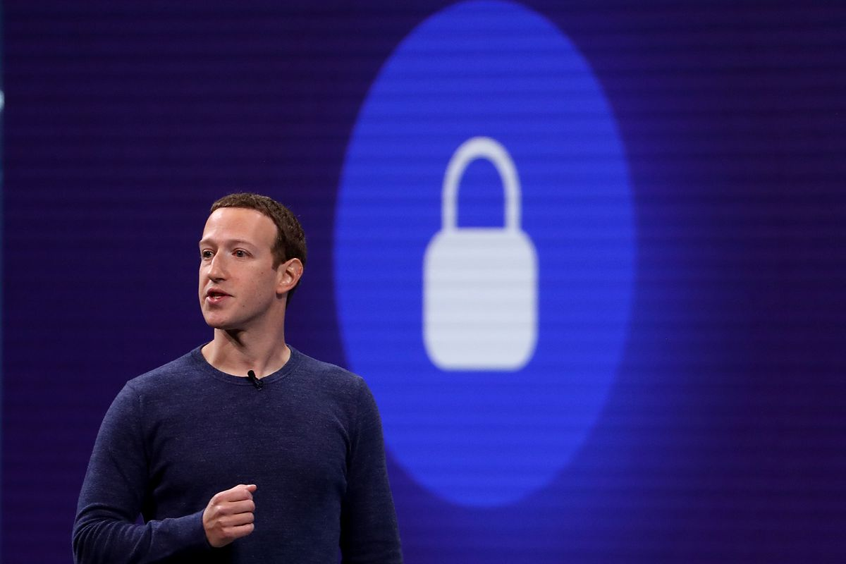 Facebook CEO Mark Zuckerberg onstage in front of an image of a padlock