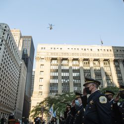 Members of the Chicago Police Department salute as a helicopter flies overhead during the commemoration of the 20th anniversary of 9/11 at the Richard J. Daley Plaza in the Loop, Saturday morning, Sept. 11, 2021.