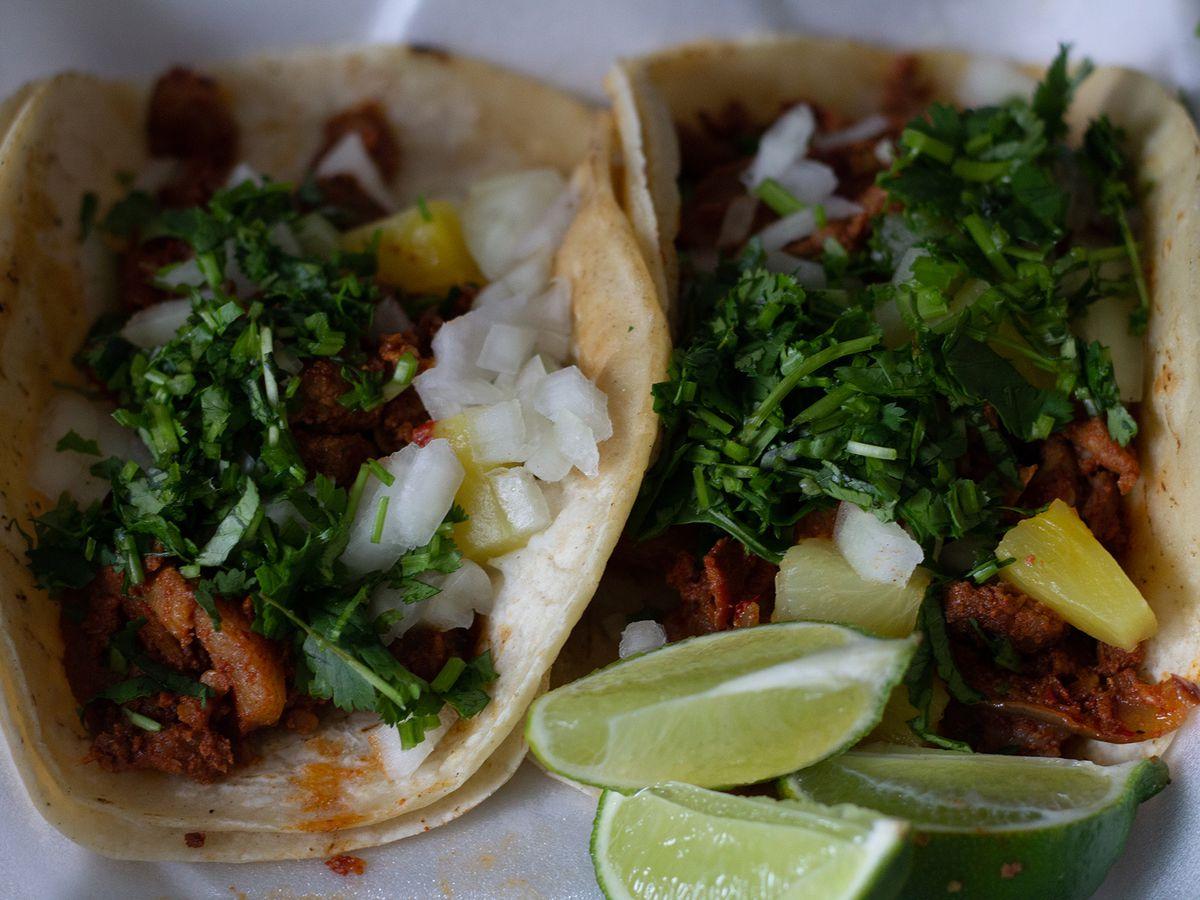 Two massive tacos al pastor, plated alongside slices of lime