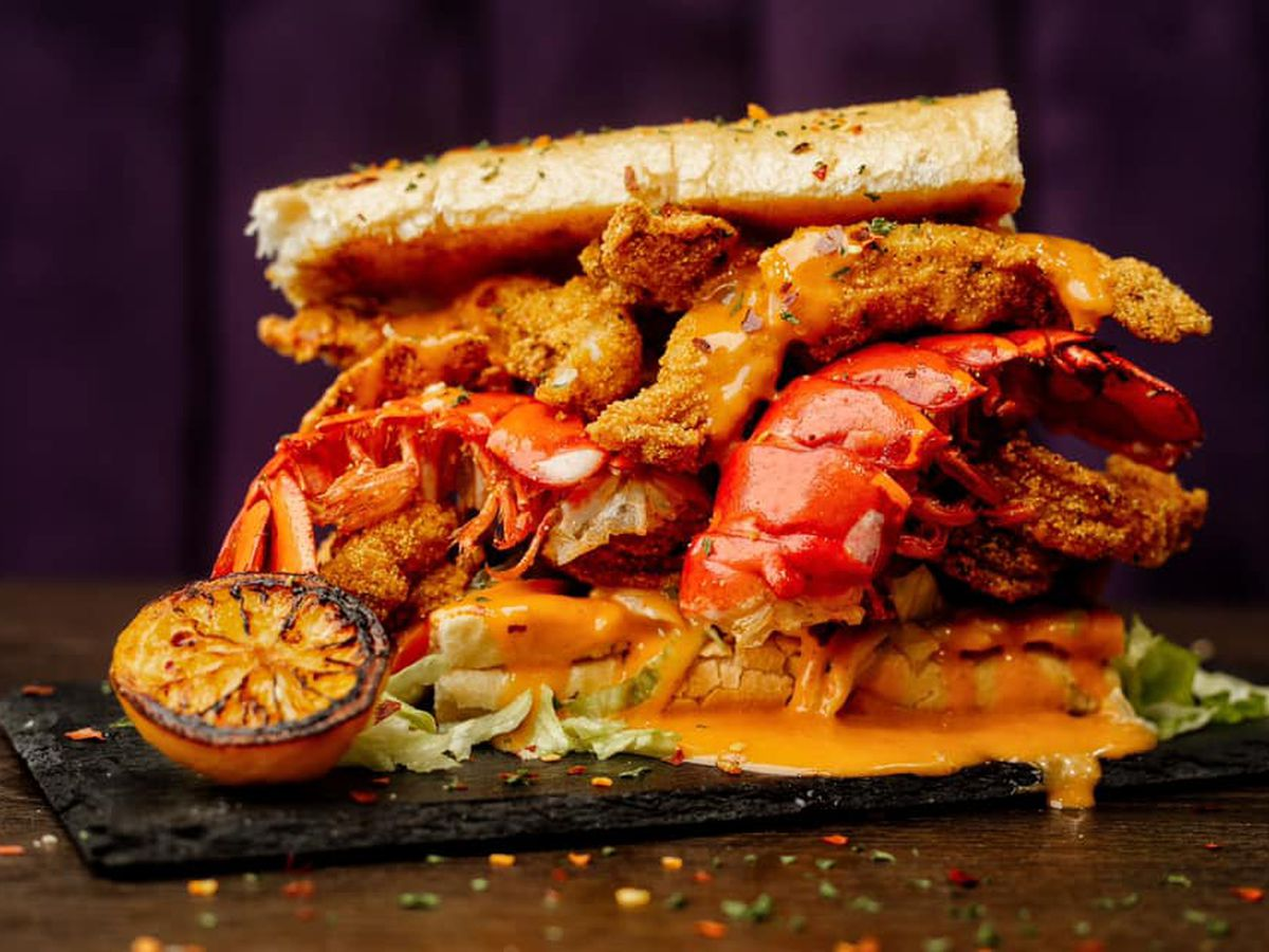 a sandwich topped with lobster tails still in the shell and fried catfish pieces