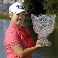 Jiyai Shin, of South Korea, holds the winner's trophy as she celebrates winning the Kingsmill Championship LPGA Tour golf tournament in Williamsburg, Va., Monday, Sept. 10, 2012. Shin won the tournament in a nine-hole playoff with Paula Creamer.