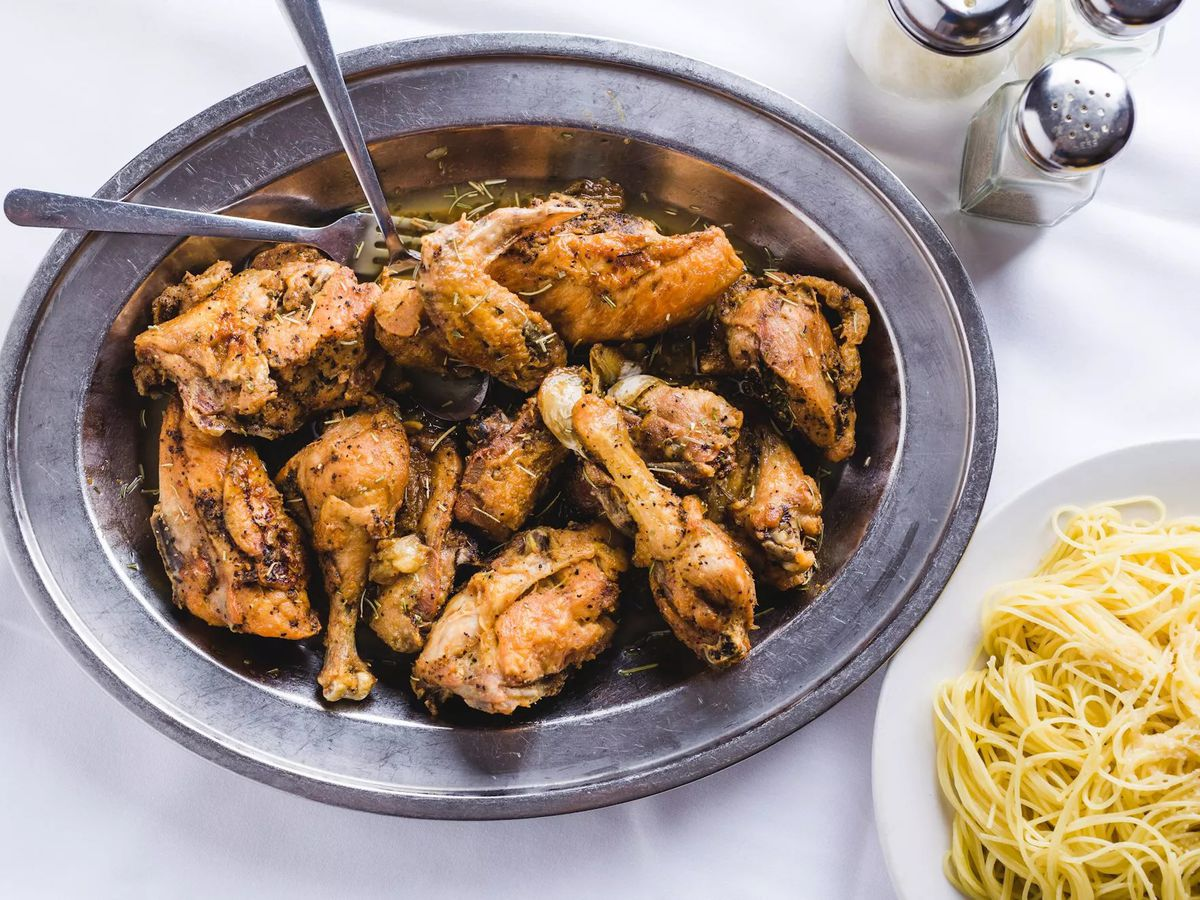 A plate of chicken drumsticks and thighs served with a plate of spaghetti