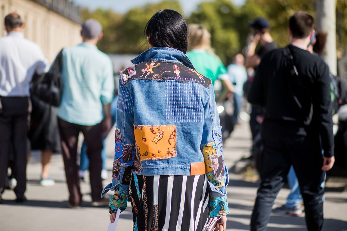 A woman in a patchwork denim jacket.