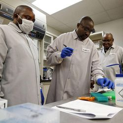 Andros Theo, left, Christopher Sakala and Katongo Chipompo of Zambia train in DNA amplification at Sorenson Forensics in Salt Lake City, Tuesday, Aug. 27, 2013.