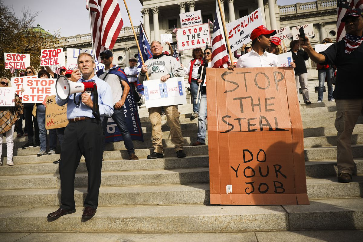 """Protesters on the steps of the Pennsylvania Capitol hold flags and signs, one of which reads, """"Stop the steal, do your job."""""""