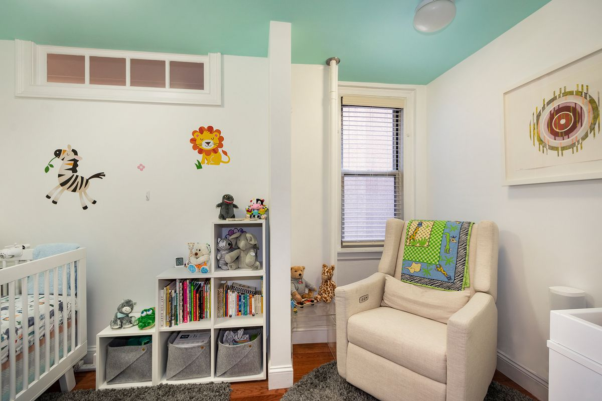 A small bedroom with a crib, animal stickers on the wall, a beige couch, and a small window.
