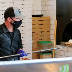 Mateo Coletti pulls an order of Oak Bread out of the oven at Oak Wood Fire Kitchen in Draper on Tuesday, Dec. 8, 2020.