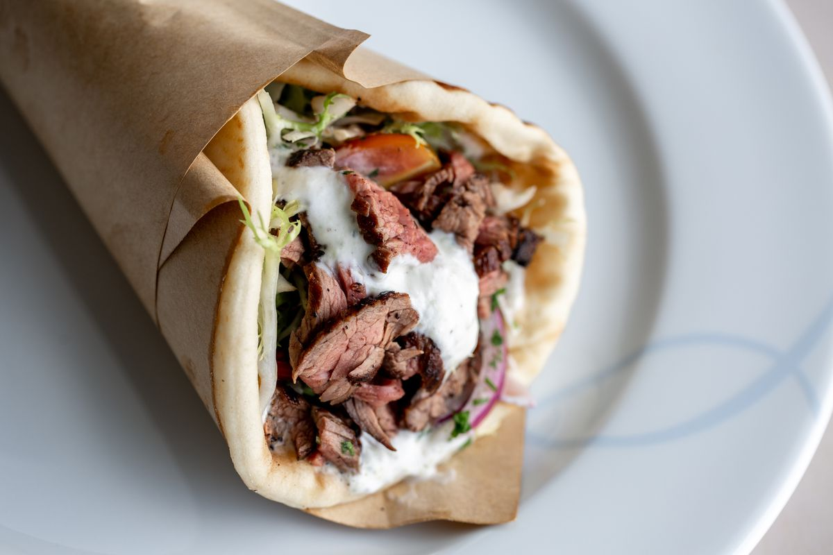 A fully cooked steak gyro wrapped inside a pita and served on a plate.