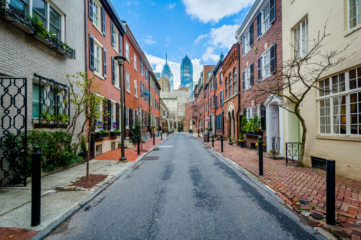 Looking down a street lined with Philadelphia rowhomes toward the Center City skyline.