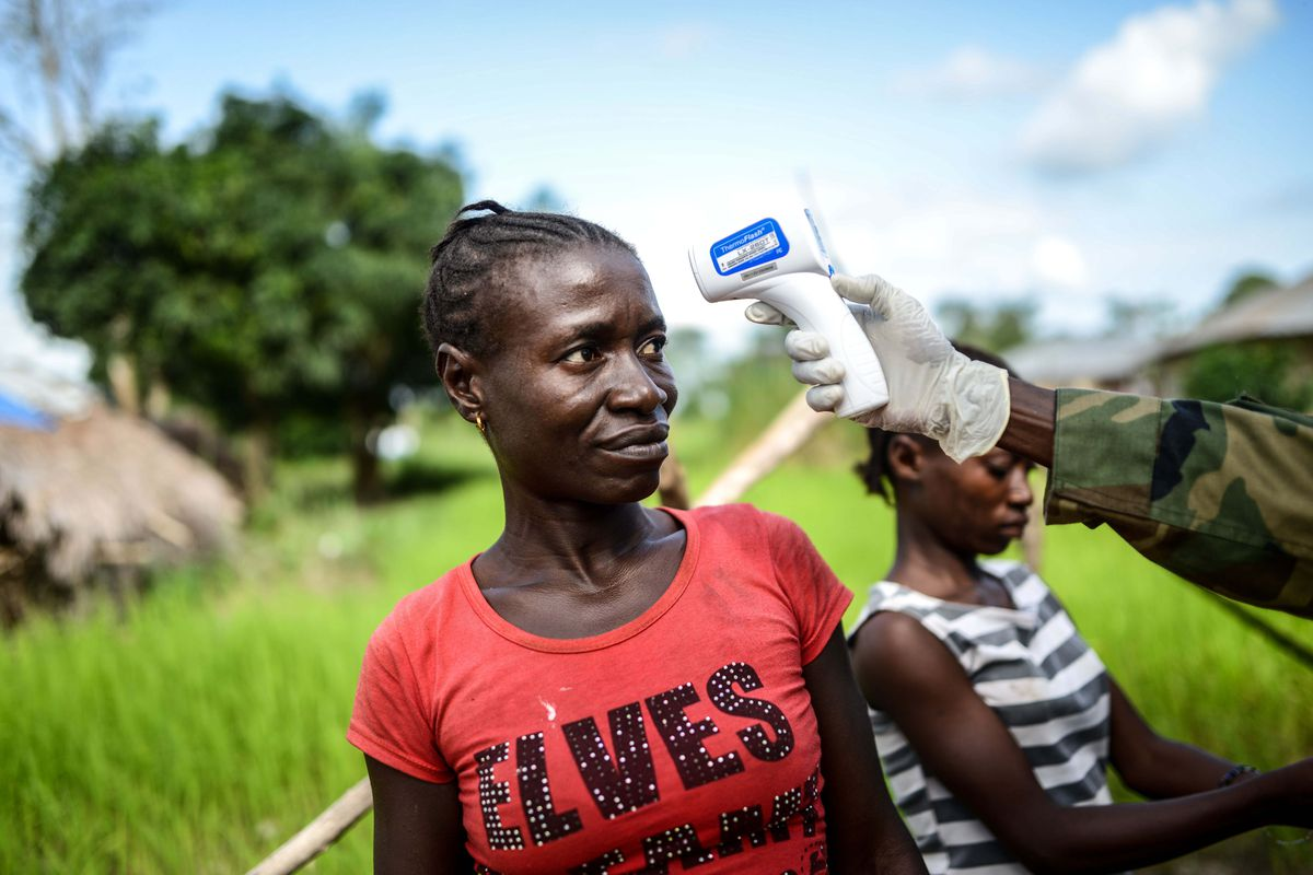 A soldier inspects a woman with an infrared thermometer for signs of fever, one of the symptoms of Ebola, at a check point in Nikabo, a village in Kenema, Sierra Leone.