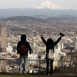 """FILE - In this file photo from Feb. 26, 2008, a young couple enjoys the view of Mount Hood looming over downtown on a spring-like day in Portland, Ore. A famous quip by Fred Armisen on the television show """"Portlandia"""" led Portland State University researchers to investigate the reality behind the comment. The quirky IFC network series pokes fun at the Oregon city's many eccentricities."""