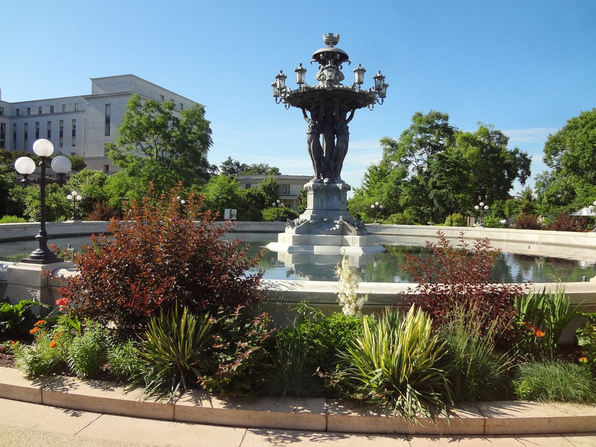 A fountain with an iron sculpture in the middle. The fountain is surrounded by landscaping.