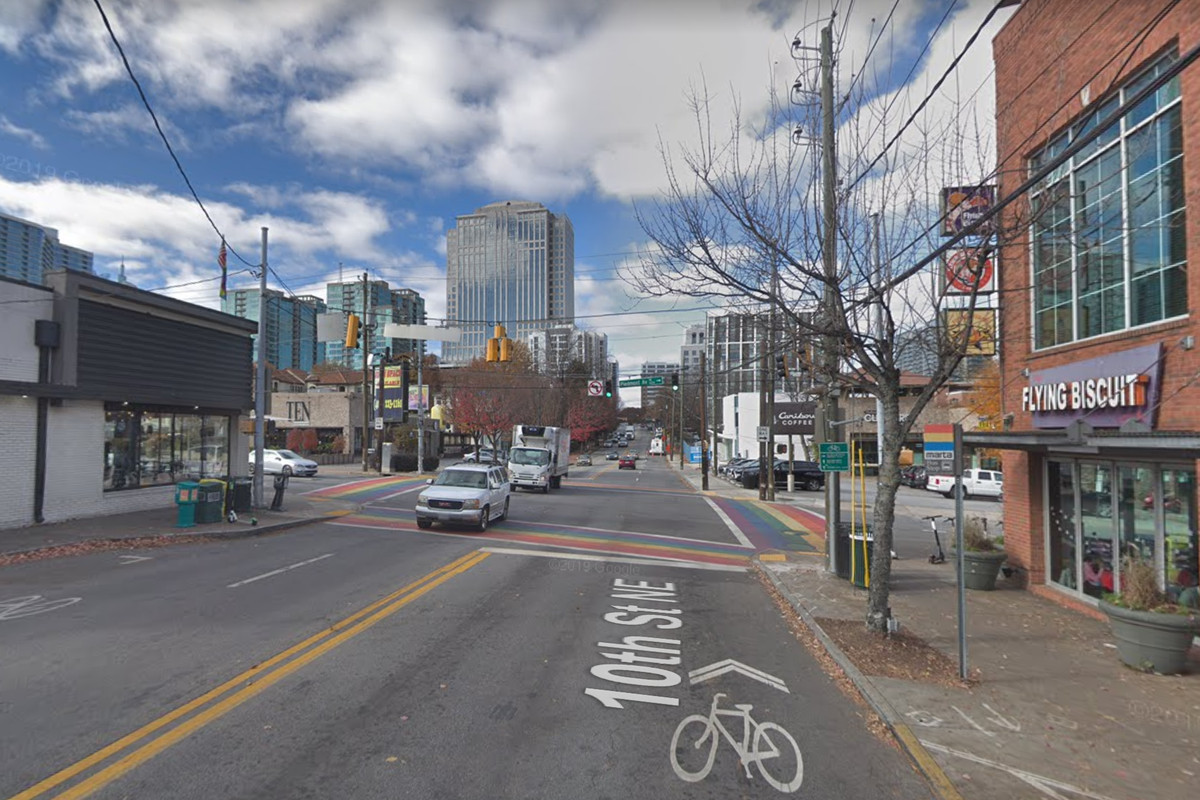 An intersection with rainbow crosswalks is flanked by local businesses.