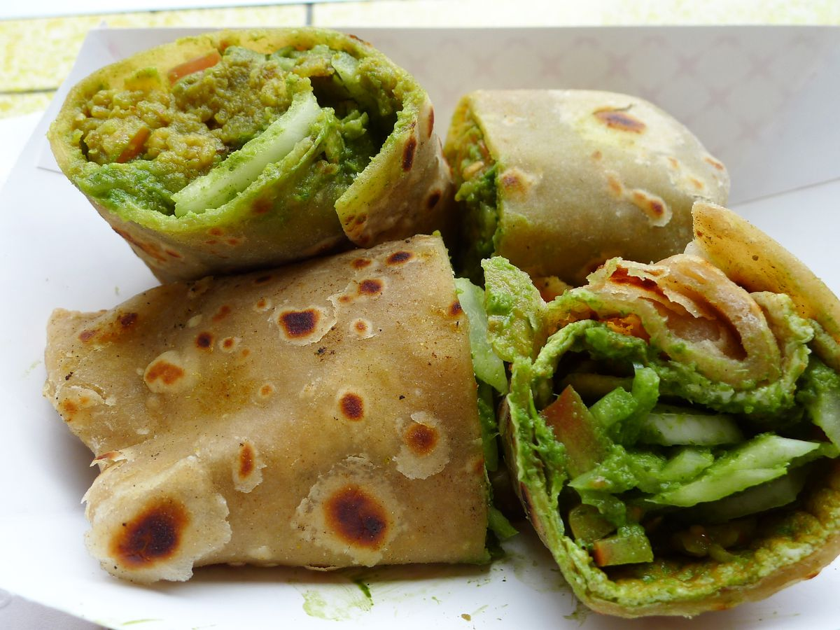 A pair or flatbread rolls, each cut in two and propped up, filled with green vegetables.