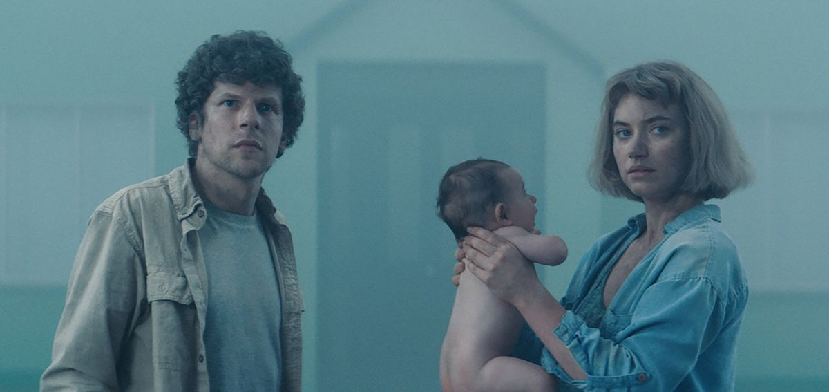 A couple hold a baby, uncomfortably.