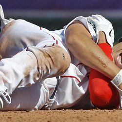Boston Red Sox' Jacoby Ellsbury grabs his right shoulder after colliding with Tampa Bay Rays shortstop Reid Brignac while being forced at second base during the fourth inning of the home opening day baseball game at Fenway Park in Boston, Friday, April 13, 2012.  Ellsbury left the game after the play.