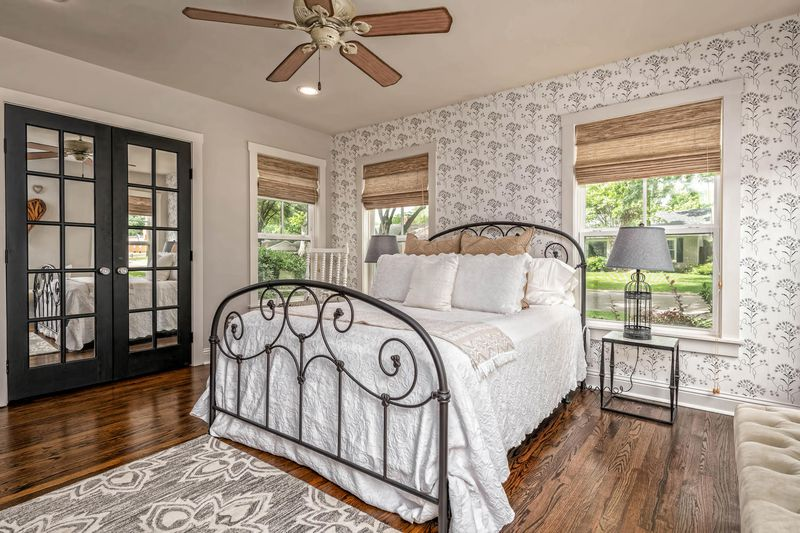 A bedroom has a wire framed bed, white comforters, wood floors, and large windows with roman shades.