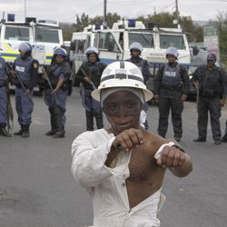 A striking platinum miner takes part in a march to the Rustenburg, South Africa, police station, Sunday, Sept. 16, 2012 to protest the heavy handed way the police are cracking down on strikers who have been off work since early last month. The march was declared illegal by the police, who prevented the protesters from entering the town, and the strikers dispersed peacefully.
