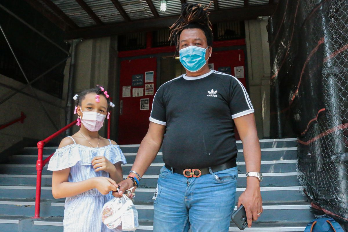 A young girl wearing a white dress, pink surgical mask, and pink and white jewelry in her hair holds her father's hand, who is wearing a black Adidas shirt, blue jeans and a blue surgical mask.