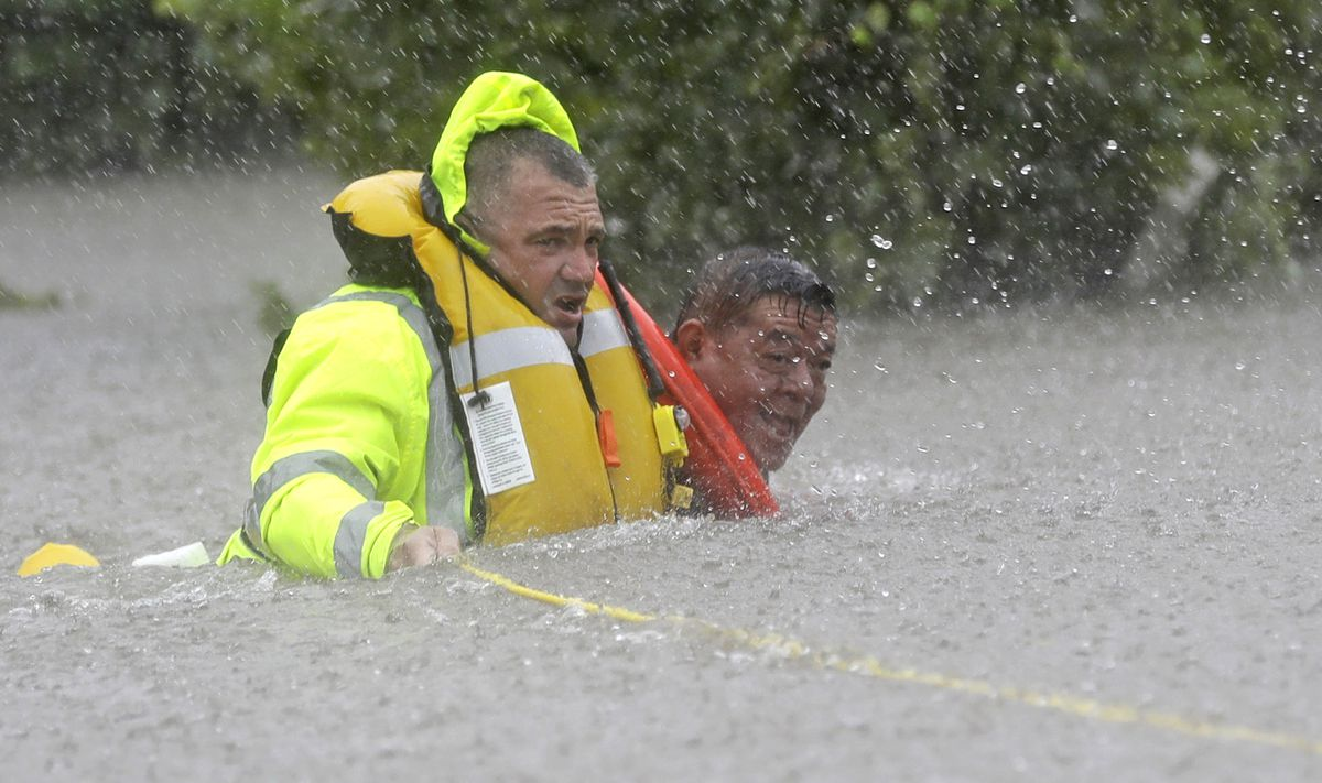 Wilford Martinez (right) is rescued from his flooded car by Harris County Sheriff's Department Richard Wagner along I-610 in floodwaters from Tropical Storm Harvey on Sunday in Houston. | David J. Phillip/Associated Press