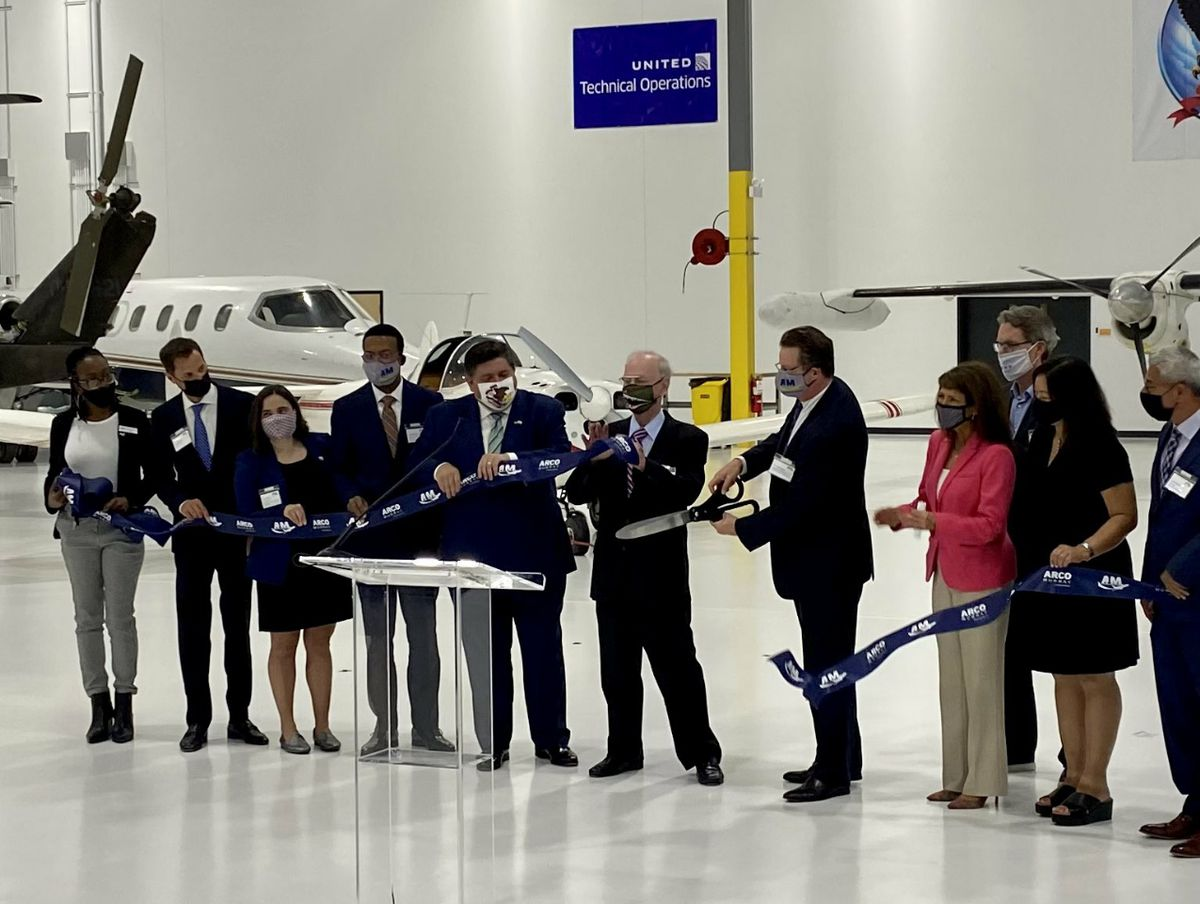 Gov. J.B. Pritzker, fifth from left, joins elected and industry officials at the ribbon-cutting ceremony at the Aviation Institute of Maintenance's new training center, at 3711 S. Ashland on Wednesday.
