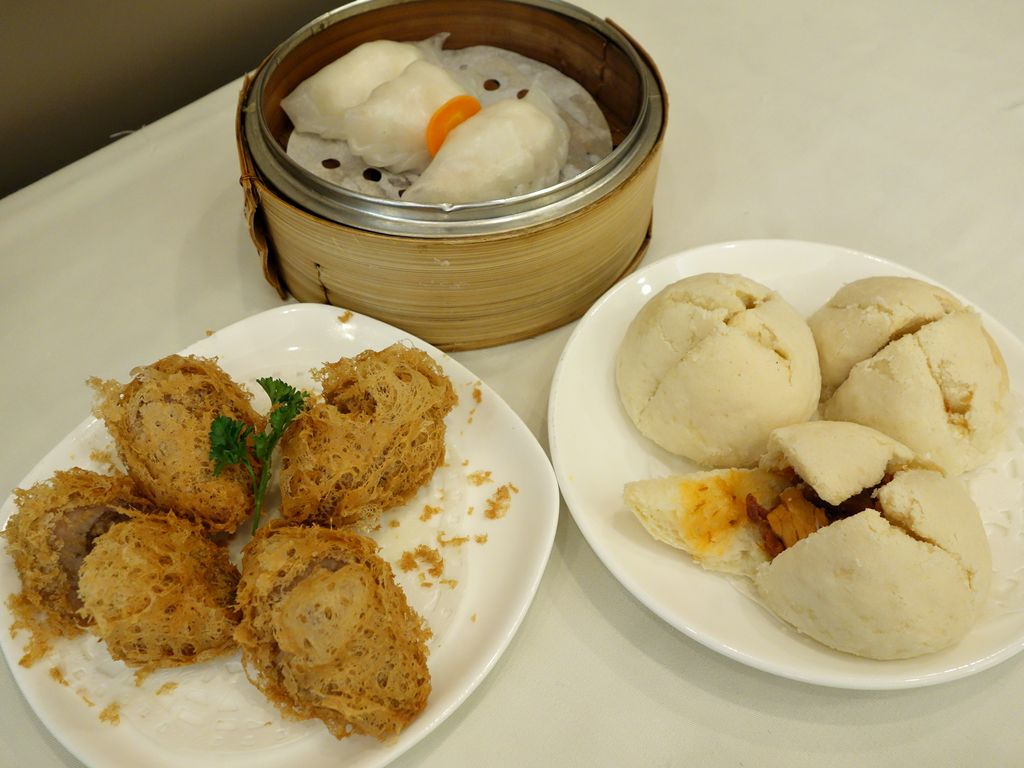 A view of dim sum dishes, including dumplings and pork buns.