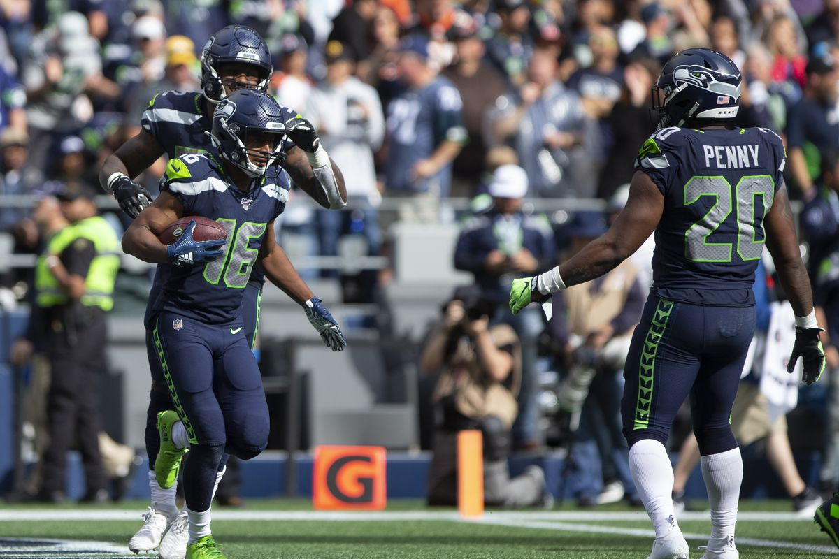 Tyler Lockett of the Seattle Seahawks celebrates a 44 yard touchdown with Chris Carson and Rashaad Penny in the fourth quarter against the Cincinnati Bengals at CenturyLink Field on September 8, 2019 in Seattle, Washington.