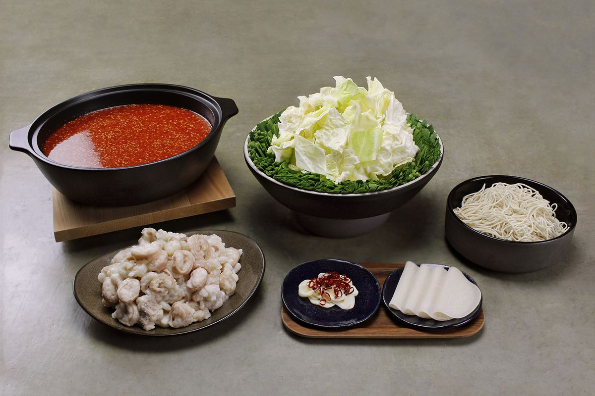A spread of dishes displaying the hot pot meal kit, with bowls of red soup, cabbage, and noodles, and plates of beef intestine, garlic, red chili pepper, and dumpling skins