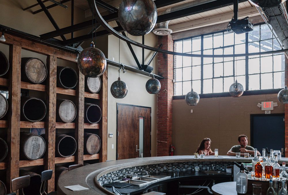A couple sits at the circular tasting room bar inside Two James Spirits.