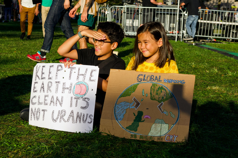 """Two kids hold signs at the Global Climate Strike in New York City. The signs read, """"Keep the Earth clean it's not Uranus,"""" and, """"Global warming is making me cry"""" with a drawing of the earth as a face shedding tears."""