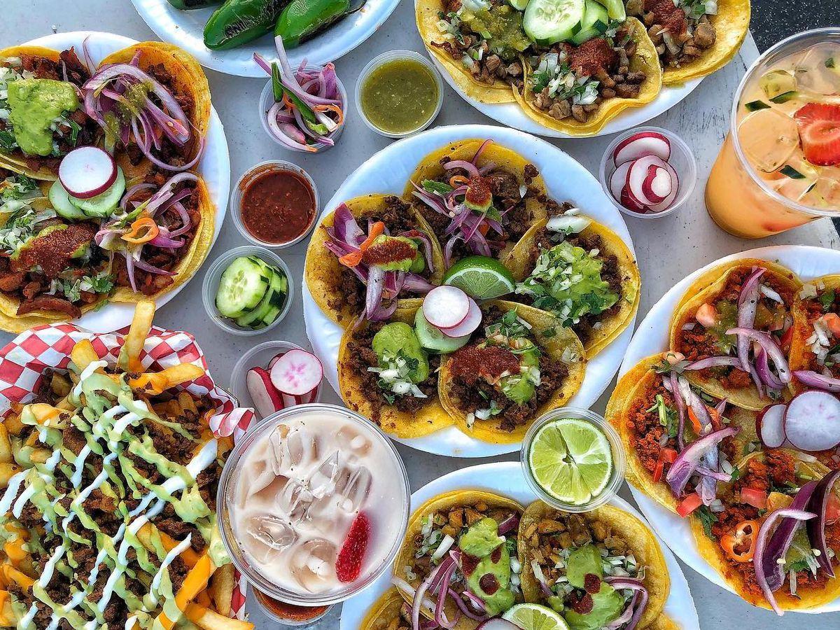 A tray filled with Tacos El Venado tacos and salsas.
