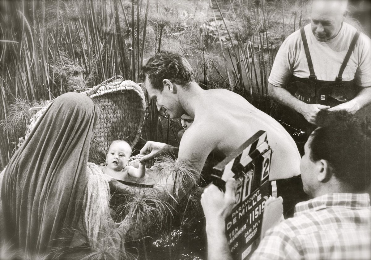 As director Cecil B. DeMille (background) looks on, the baby Moses, played by Fraser Heston, is tended to by his famous real-life dad Charlton Heston during this scene being filmed on the backlot of Paramount Studios in 1955.
