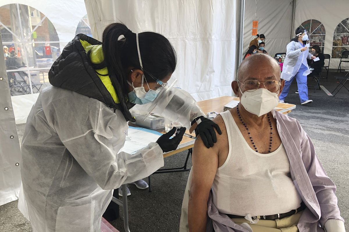 In this Feb. 8, 2021, file photo, Victor Villegas, 78, right, receives a COVID-19 vaccine shot from a health care worker at a vaccination site in the Mission district of San Francisco.