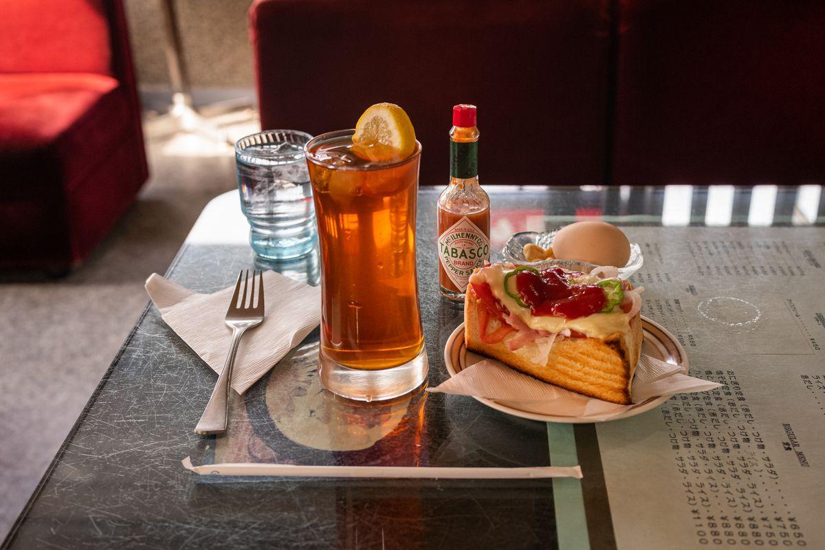 An iced tea next to a slab of pizza toast at Yashiro