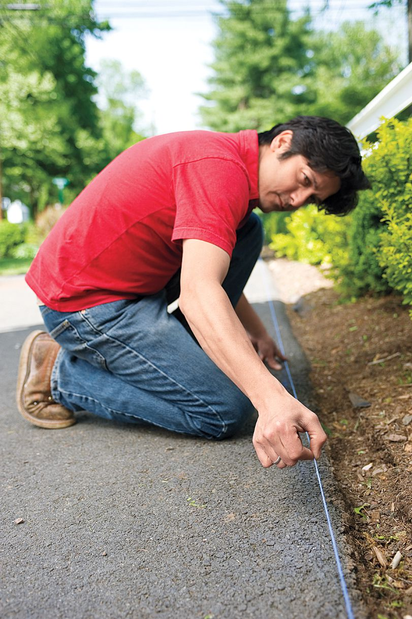 Man Marks Cut Line To Prepare For Cutting Asphalt For Driveway Edging