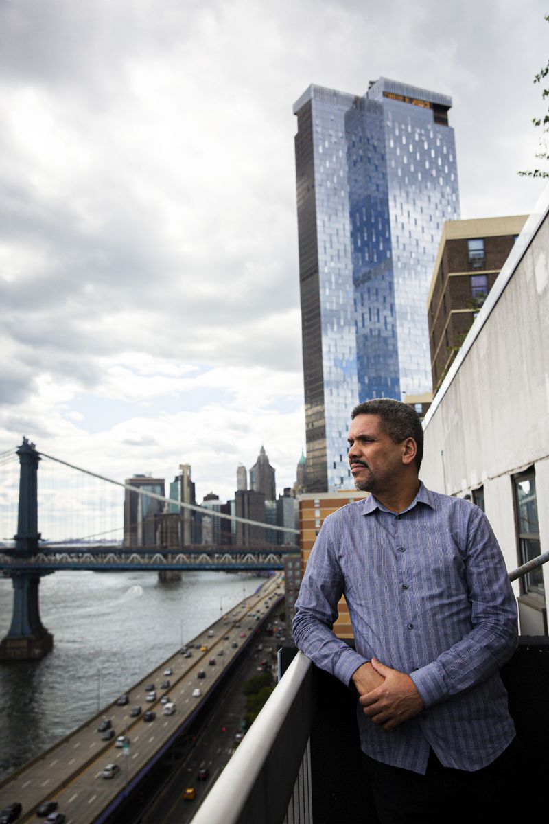 A man stands on the balcony of his apartment that overlooks the river in the New York neighborhood of Two Bridges; a bridge and skyscrapers are in the background.