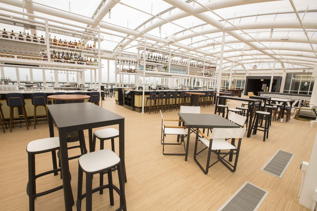A spacious rooftop bar and deck enclosed in glass walls.