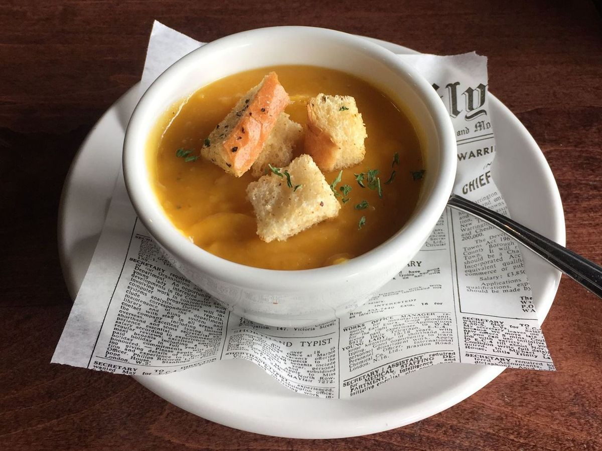 A white cup of soup with a thick, orangish soup topped with three croutons. The soup cup is on a saucer lined with fake newspaper on a wood table.