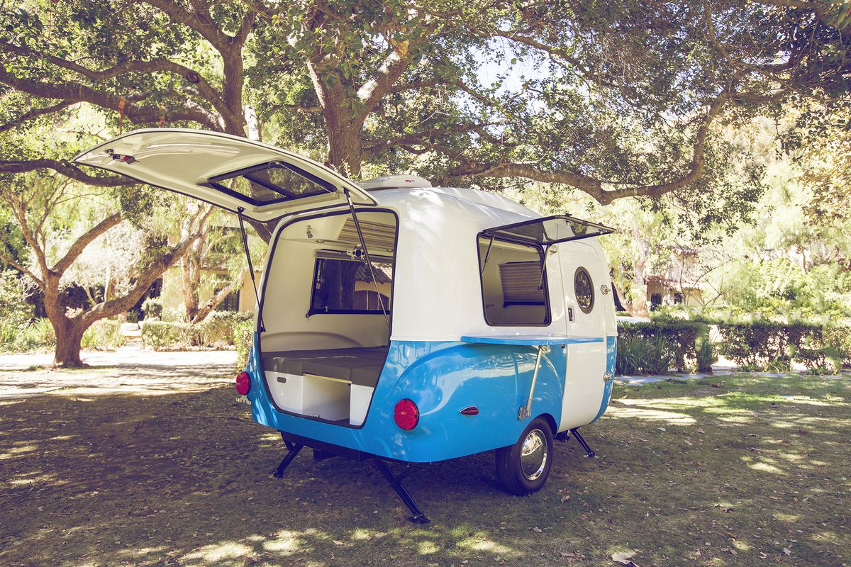 A blue and white fiberglass camper with the rear door and side window open.