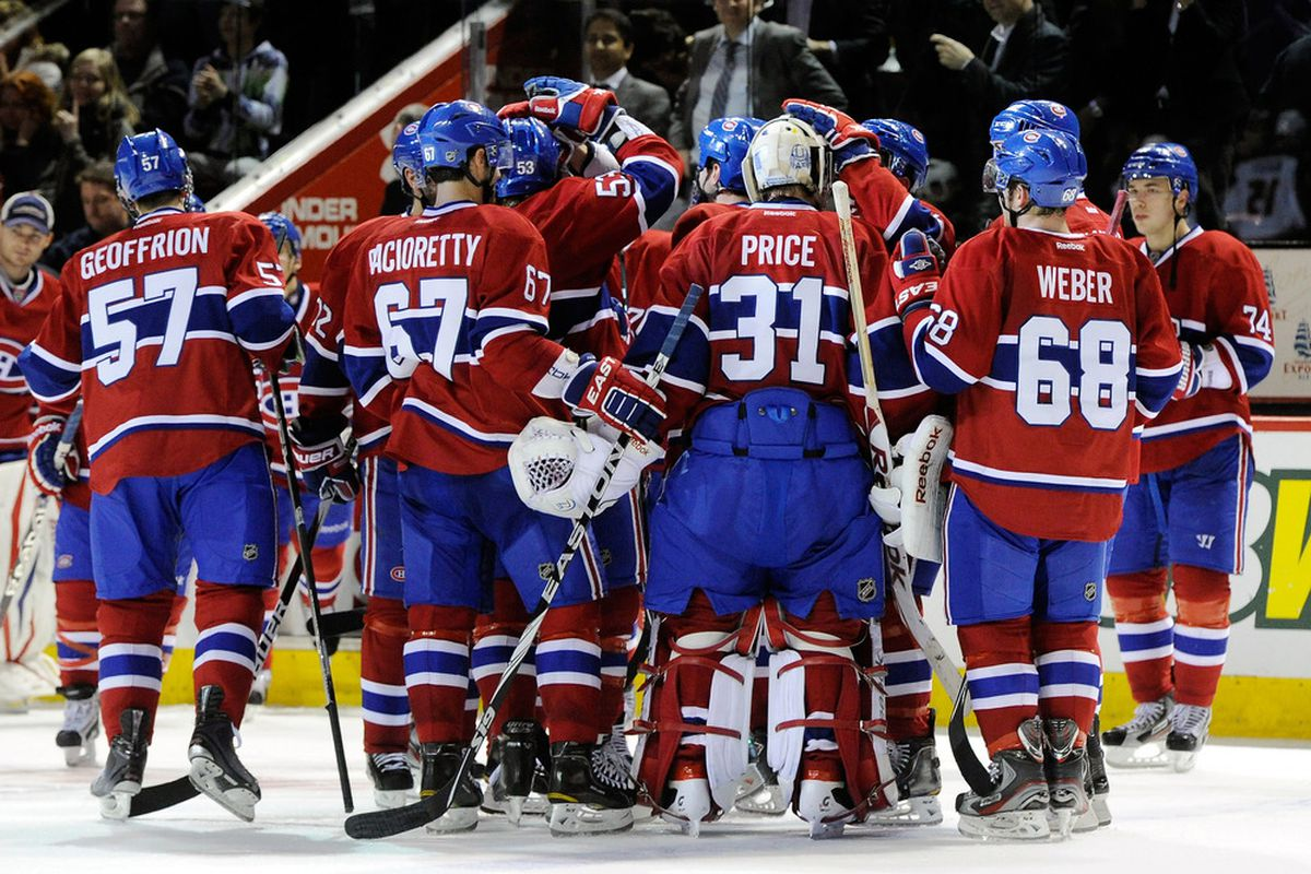 The Habs gather around in celebration that they are still ever so close to costing JS $40.  (Photo by Richard Wolowicz/Getty Images)