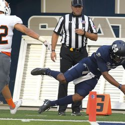 Utah State quarterback Kent Myers (2) dives into the end zone for a touchdown as Idaho State defensive back Nikko Hayes (22) watches during an NCAA college football game Thursday, Sept. 7, 2017, in Logan, Utah. (Eli Lucero/Herald Journal via AP)
