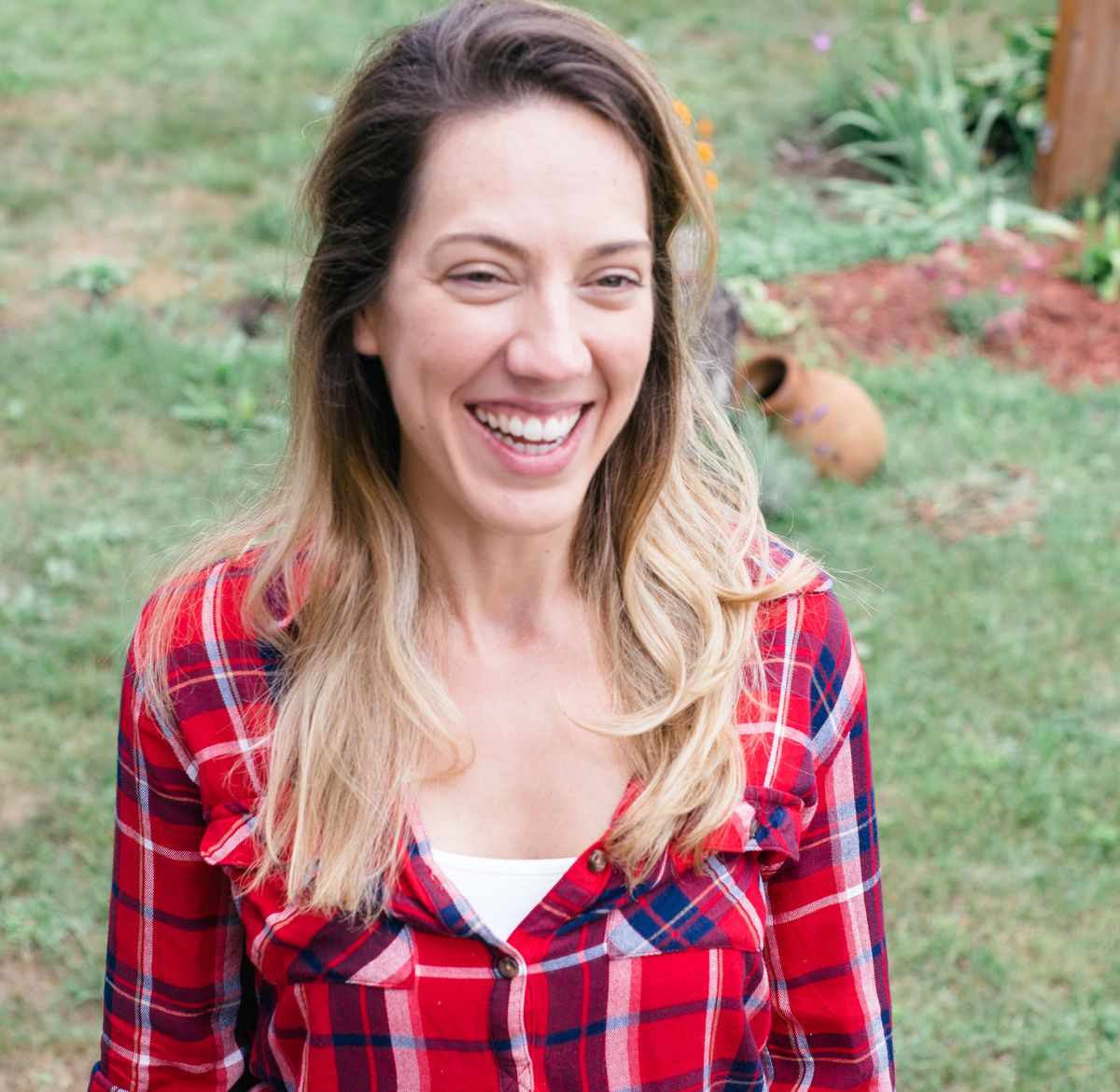Belen is smiling, standing on green grass, wearing a red plaid shirt with a white undershirt