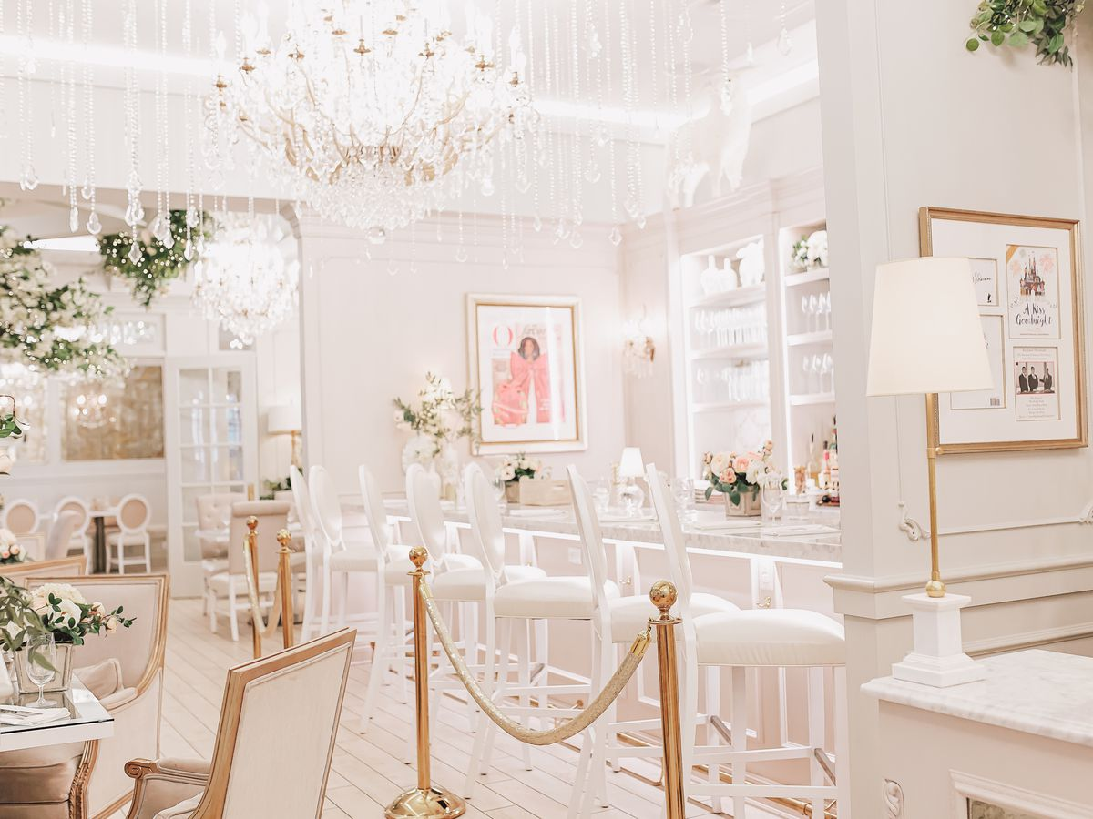 An all-white interior with a marble bar and seating, four-tops with large floral centerpieces, chandelier, gold velvet ropes and bright tile flooring