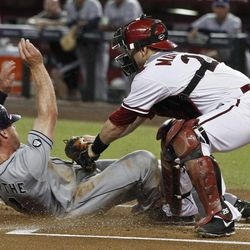 San Diego Padres' Logan Forsythe, left, scores a run as he slides under the tag of Arizona Diamondbacks' Miguel Montero during the first inning during a baseball game Tuesday, Sept. 18, 2012, in Phoenix.