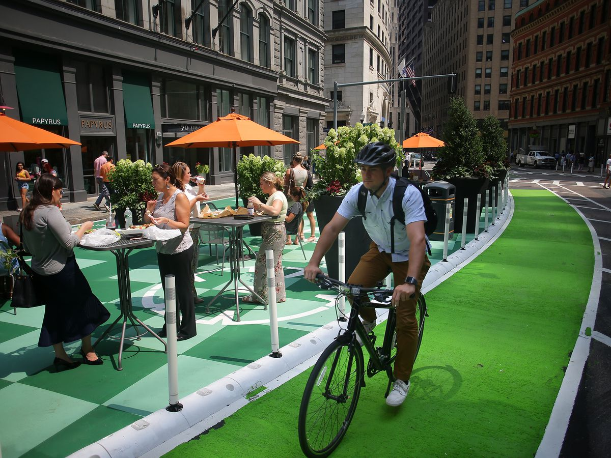 A bicyclist riding along a pedestrian plaza with diners at tables to his right.