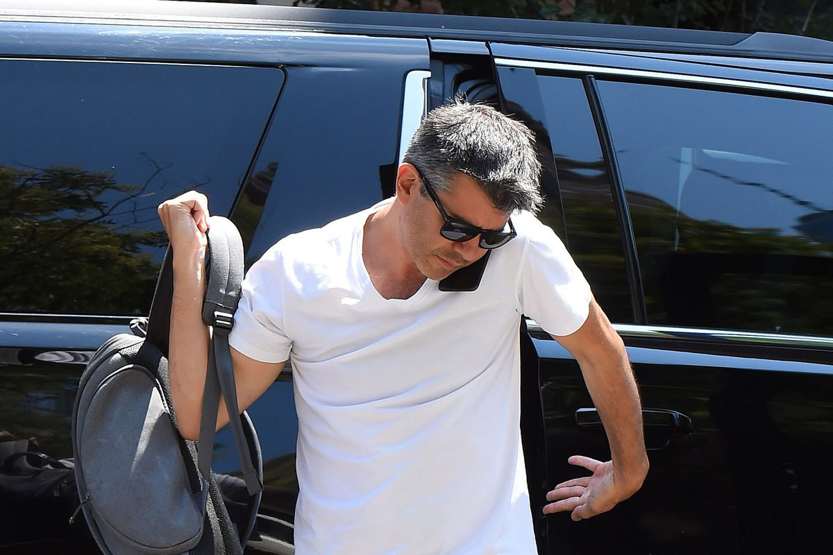 Former Uber CEO Travis Kalanick exits a black SUV while holding a bag in one hand and his phone under his chin.