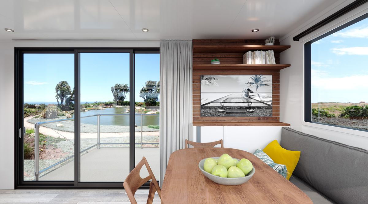 The trailer's wooden dining room table and bench seat sits in front of an eight-foot sliding glass door with access out to the patio.